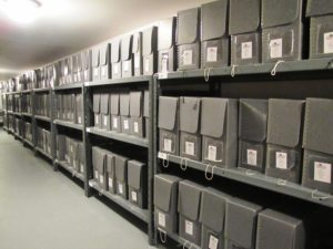 Archive files stacked on shelves in grey boxes