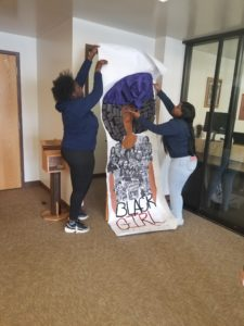 Metro High School students installing door art in the AAMI lobby