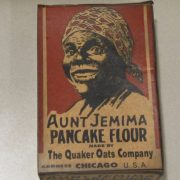 Small rectangular box of Aunt Jemima pancake flour. Box has the text: [AUNT JEMIMA/ PANCAKE FLOUR / MADE BY/ THE QUAKER OATS COMPANY/ ADDRESS CHICAGO U.S.A.] The front and back of the box has a black and light sepia colored drawing of Aunt Jemima with a plaid type scarf covering her head. The background color of the box is a burnt sienna.