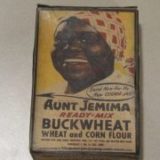 "Cardboard salesman's sample box of Aunt Jemima Ready-Mix Buckwheat pancakes. Front of box has yellow background with shoulders-up image of ""Aunt Jemima"" character. She is wearing white clothing and a red and white checked head scarf. Black and red printing superimposed on her clothing reads, [AUNT JEMIMA / READY-MIX / BUCKWHEAT / WHEAT and CORN FLOUR / PREPARED WITH CORN SUGAR, PHOSPHATE, SODA, SALT, RICE FLOUR, AND DEFATTED MILK SOLIDS / WEIGHT 1 LB. 4 OZ. NET / MANUFACTURED BY The Quaker Oats Company ADDRESS CHICAGO U.S.A.]."