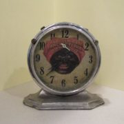 Metal alarm clock with image of Aunt Jemima character on face. Clock is metal with a glass plate over the face. Glass plate is attached to clock with three screws. Clock is round and is screwed to a base with two screws. Face of clock has numbers 1-12, black hour and minute hands, and smaller white hand above. Hour and minute hands are attached at the nose of an image of Aunt Jemima, an African American woman with a red head scarf. Printing on head scarf reads, [AUNT JEMIMA'S / PANCAKE FLOUR / ASK YOUR GROCER]. Bottom of face has printing reading, [THE LUX CLOCK MFG. CO. INC. LEBANON, TENN., U.S.A.]. Top of clock has two metal switches, each of which is associated with two white rectangles. Faint printing on second rectangle from right reads, [STEADY]; printing is illegible on far right rectangle and gone from two left rectangles. Back of clock has two winding mechanisms, one reading [ALARM] and the other [TIME]. Two other dials have no labels. An arc-shaped hole in the top proper left of the back has an [S] at one end and an [F] at the other. There is a foot at the bottom center to support the clock if it is tipped back. Printing at bottom proper left of back reads, [PATENTED / JUNE 9, 1908 / DEC. 15, 1908 / AUG. 29, 1911 / NOV. 9, 1920 / PATENTS PDG.]. Clock works.