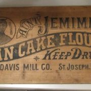 Wooden panel from a shipping crate. Has black stamped image and words. Has a circle with crude woodcut type image of Aunt Jemima character (an African American woman in a head scarf), with the words [TRADEMARK] and [REGISTERED] on the left and right of the image, respectively. Writing reads, [AUNT JEMIMA'S / PAN CAKE FLOUR / KEEP DRY / R.T. DAVIS MILL CO. ST. JOSEPH. MO.]. Both the word [Aunt] and the words [Pan Cake Flour] are on banner backgrounds. There are nail holes on the right and left extreme ends of the panel: four holes per side. There are three nail holes, two with broken nails in them, on the bottom of the panel. There is one nail in the top of the panel; its point comes through the front of the panel just above the word [Aunt].