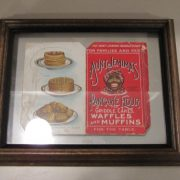 This a needlebook in the shape of an Aunt Jemima's Pancake Flour box. The booklet is opened and placed between glass then encased in a brown wood frame. The right side of the book cover is red and the image of Aunt Jemima is in the center. The patent number on the right side is [51056] and the serial number underneath is [1462]. On the front, the inscription at the top includes the words [THE AUNT JEMIMA NEEDLE BOOK], and below the words [PANCAKE FLOUR/ FOR/ GRIDDLE CAKES/ WAFFLES/ AND MUFFINS/ FOR THE TABLE] On the left side of the cover are pictures of pancakes, waffles and muffins. The back right side has the words [NECESSITY]] at the top and below that is a sheet in which three needles are inserted. Below that is a statement about the economic value and product guarantee. On the left side, a title states [A HOUSEHOLD]. Below are drawings of what appears to be Aunt Jemima's family. Over their heads are the words [ISE IN TOWN HONEY]. Information follows about ingredients, how to acquire recipes, and cloth rag dolls in color that represent Aunt Jemima's family. The pictures of the family are a stylize stereotypical depiction of African Americans.