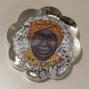 The image of Aunt Jemima is encased in a small scalloped edge, circular glass paper weight. The image is in color. She has an orange colored head scarf with dots and the neck dress has yellow background and orange stripes. The face of Aunt Jemima seems is etched in black, the face is fat, eyes are large, with a long narrow nose and wide grin.