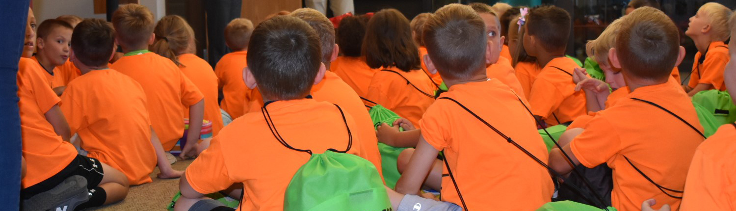 Children sitting in a group during a school tour of the museum.