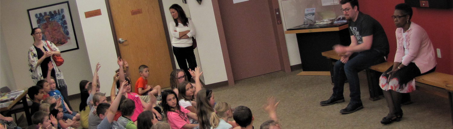 Children sitting in a group raising their hands during a school tour of the museum.